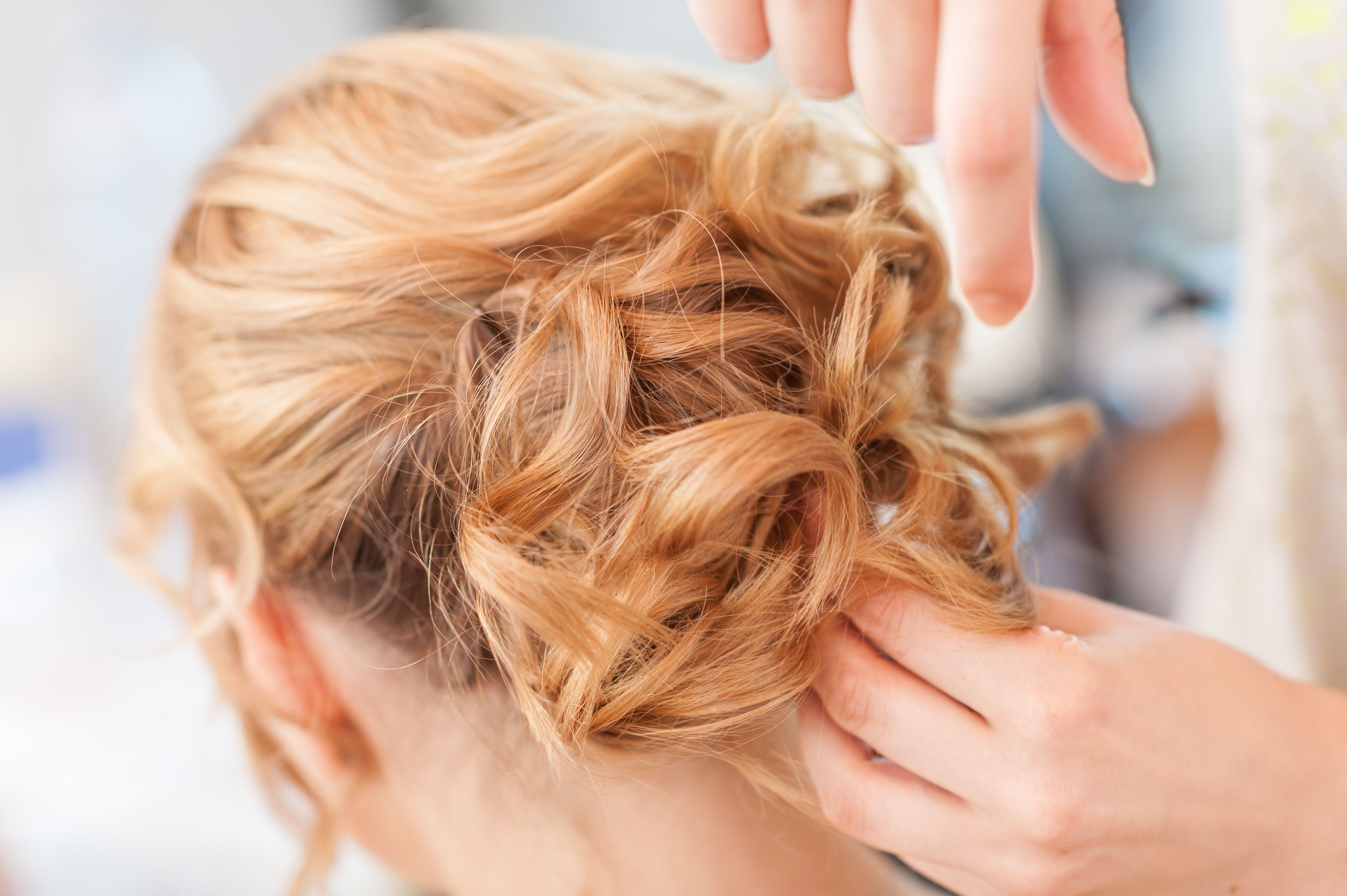 Image of a hair stylist inserting hair pins into a model's curled and pulled back hair.