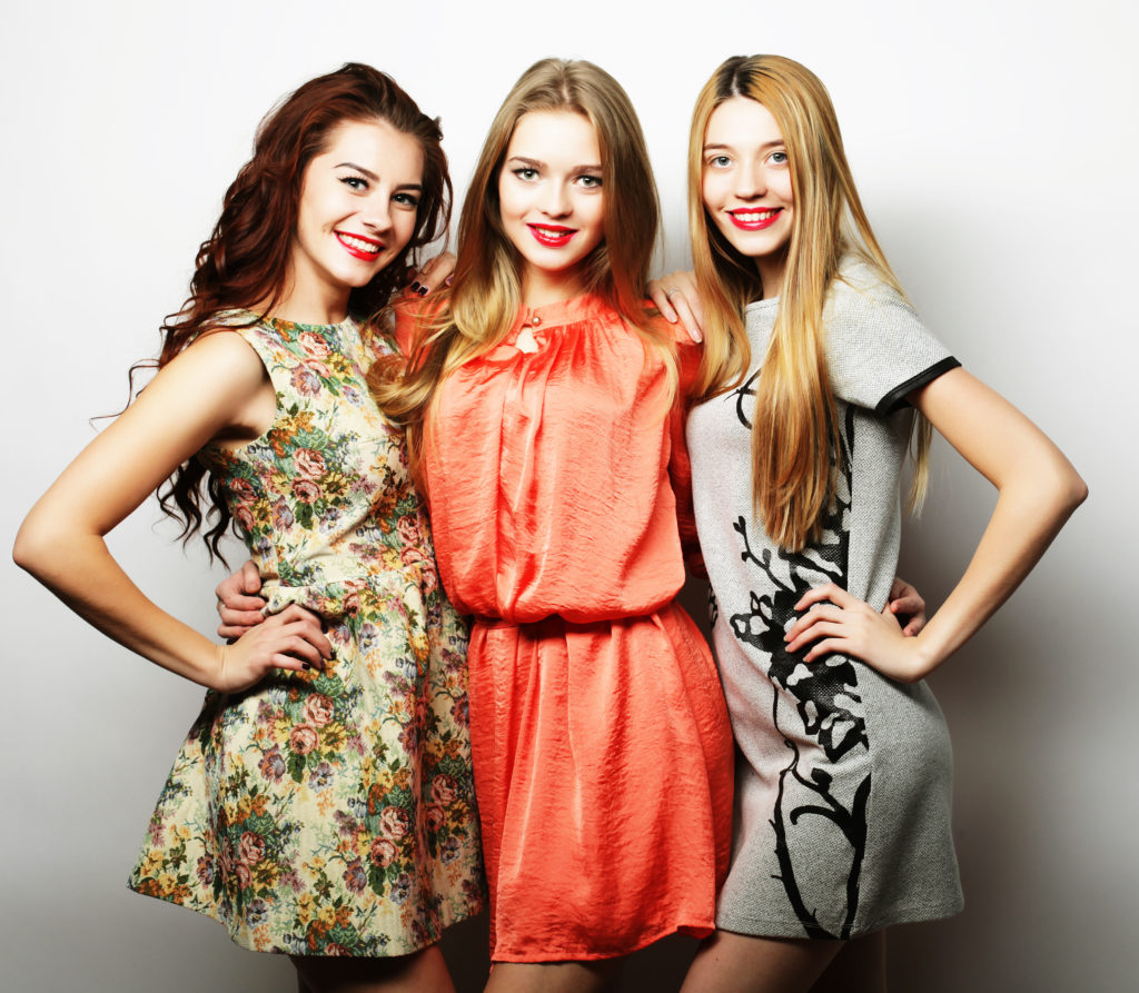Three stylish hipster girls best friends.Standing together and having fun. Over gray background.